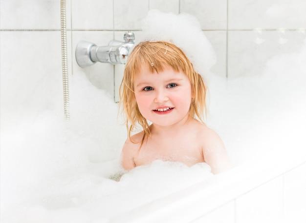 Kleines mädchen badet in einem bad mit schaum und luftblasen