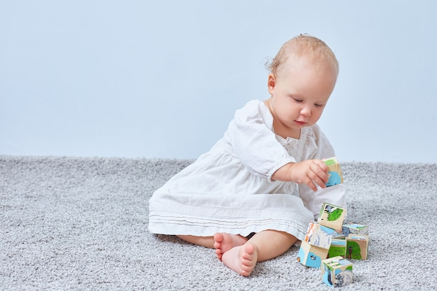 Kleines mädchen baut eine pyramide von holzklötzen auf dem teppich. speicherplatz kopieren.