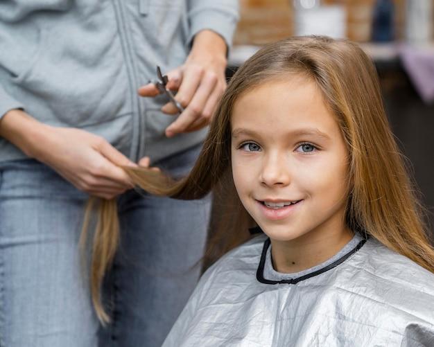 Kleines mädchen bei einem termin mit ihrem friseur, der einen haarschnitt bekommt