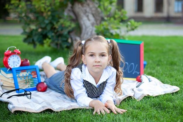 Kleines mädchen beim mittagessen und lernt auf einer wiese im park.