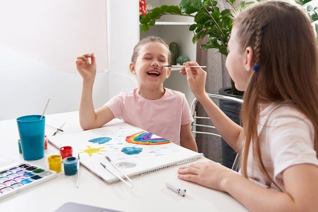 Kleines mädchen bekommt ihr gesicht von älterer schwester am tisch gemalt