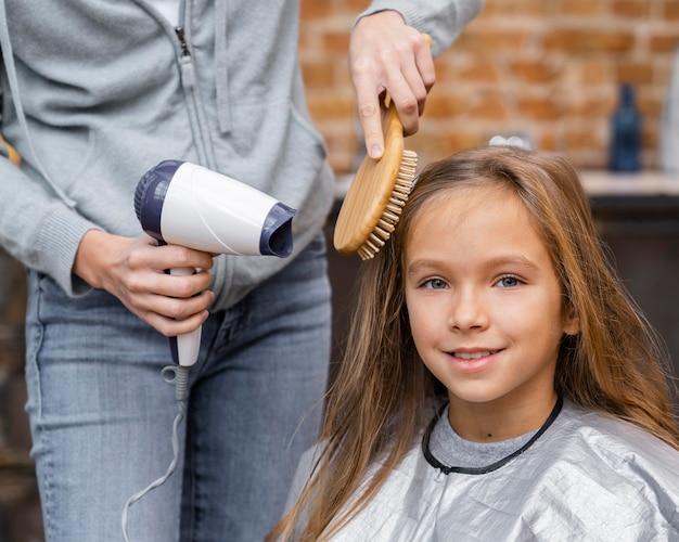Kleines mädchen bekommt ihre haare gebürstet und getrocknet