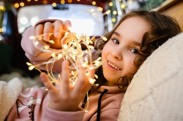 Kleines mädchen beleuchtetes gesicht, das warme gelbe lichter der girlande am weihnachts- und neujahrshintergrund hält