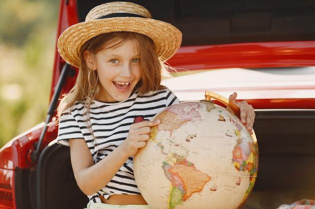Kleines mädchen bereit, in den urlaub zu fahren. kind in einem roten auto. mädchen mit globus und hut.