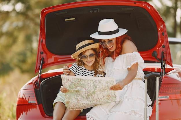 Kleines mädchen bereit, in den urlaub zu fahren. mutter mit tochter, die eine karte untersucht. reisen mit dem auto mit kindern.