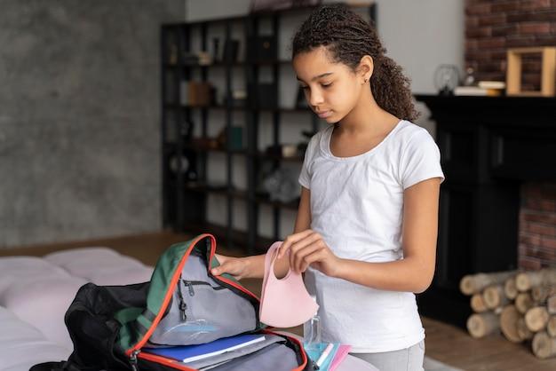 Kleines mädchen bereitet ihren rucksack für die rückkehr zur schule vor
