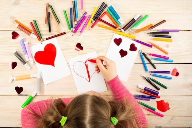 Kleines mädchen bereitet karten mit herzen für valentinstag vor