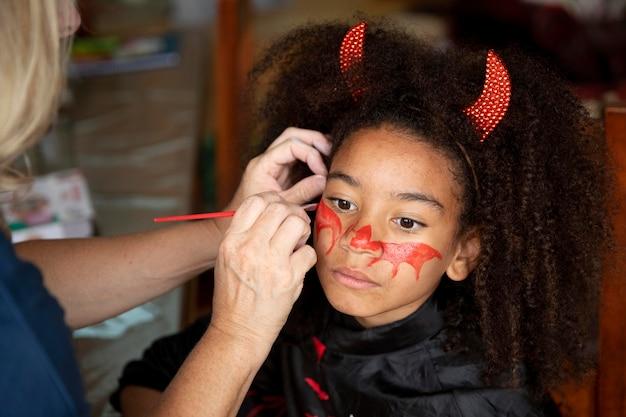Kleines mädchen bereitet sich auf halloween mit einem teufelskostüm vor