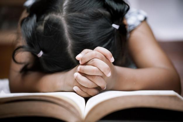 Kleines mädchen betet mit einer heiligen bibel
