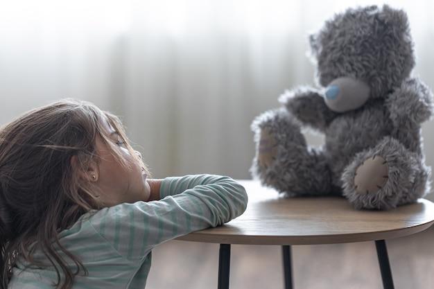 Kleines mädchen betrachtet ihren teddybären, ein kind mit einem lieblingsspielzeug auf einem unscharfen hintergrundkopierraum.
