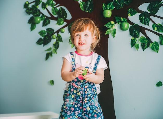 Kleines mädchen bleibt in der nähe des gemalten baumes und hält äpfel in händen
