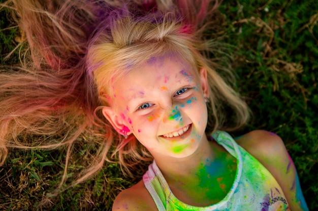 Kleines mädchen blond in farben holi lächelnd im gras liegend