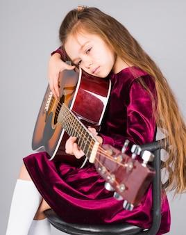 Kleines mädchen, das akustikgitarre auf stuhl spielt