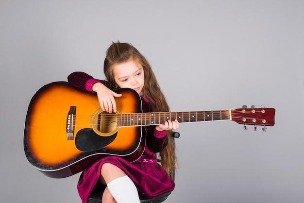 Kleines mädchen, das akustikgitarre spielt