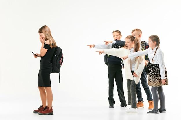 Kleines mädchen, das allein steht und eine mobbinghandlung erleidet, während sich kinder im hintergrund lustig machen. trauriges junges schulmädchen, das auf studio gegen weißen hintergrund steht.