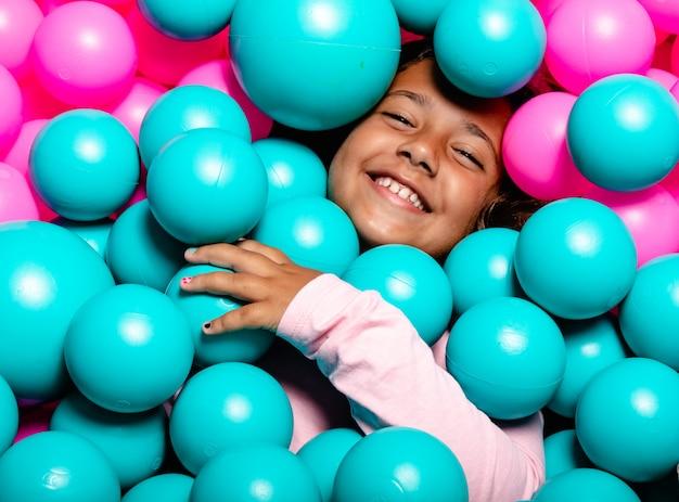 Kleines mädchen, das am rosa und blauen ballpool lächelt und spielt