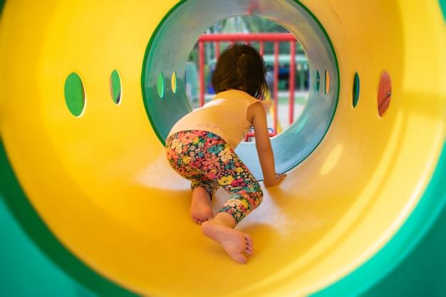 Kleines mädchen, das am spielplatz spielt. kind, das draußen sonnigen sommer- oder frühlingstag genießt.