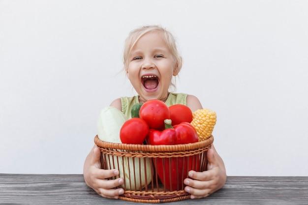 Kleines mädchen, das am tisch sitzt, umarmt einen korb voller frischem gemüse und freut sich