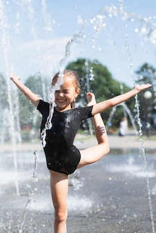 Kleines mädchen, das am wasserbrunnen spielt