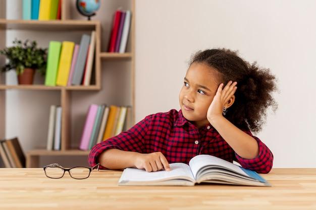 Kleines mädchen, das an das gelesene buch denkt