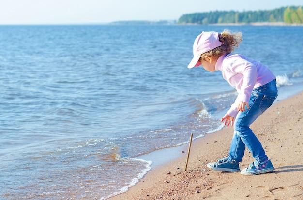 Kleines mädchen, das an der küste im sand spielt