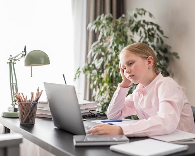 Kleines mädchen, das an der online-klasse drinnen teilnimmt