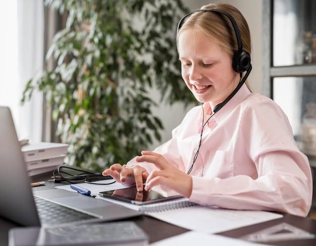 Kleines mädchen, das an der online-klasse teilnimmt, während es tablette benutzt