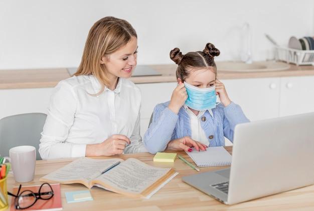 Kleines mädchen, das an einer online-klasse eine medizinische maske aufsetzt
