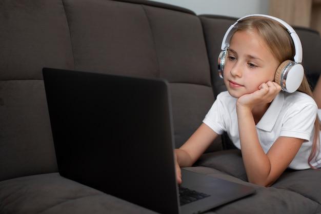Kleines mädchen, das an online-kursen teilnimmt, während es kopfhörer verwendet