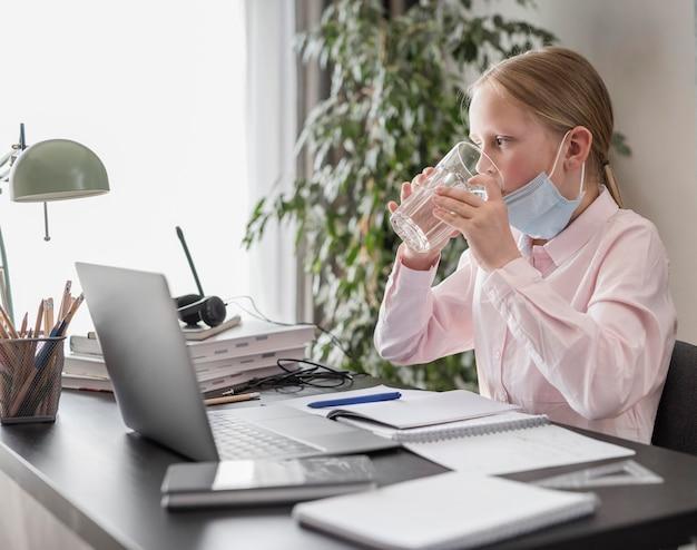Kleines mädchen, das an online-unterricht und trinkwasser teilnimmt