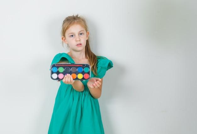 Kleines mädchen, das aquarellfarben mit pinsel im grünen kleid hält