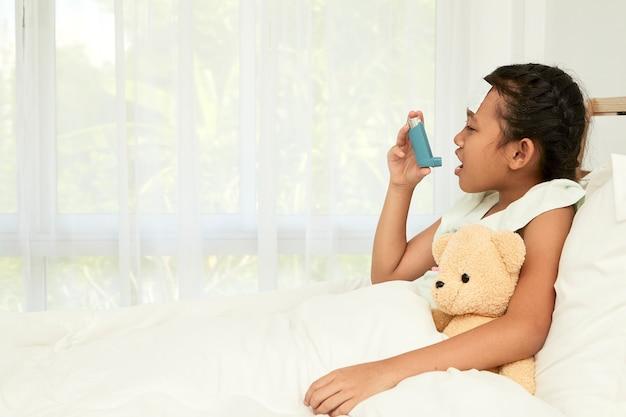 Kleines mädchen, das asthma-inhalator verwendet