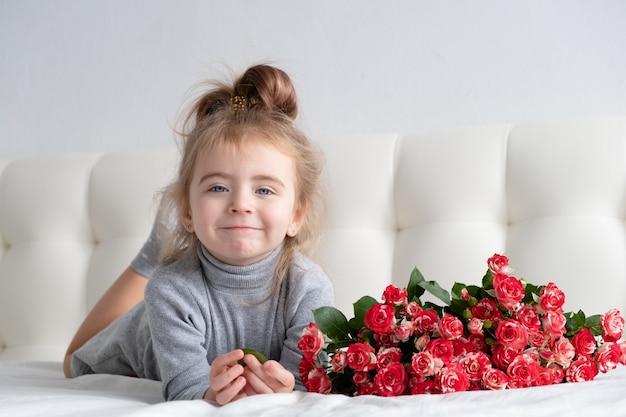 Kleines mädchen, das auf bett mit blumenstrauß der rosa rosen liegt.