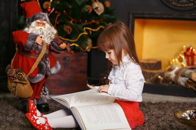 Kleines mädchen, das auf boden in schönen weihnachtsdekorationen sitzt. mädchen, das ein märchenspielzeug santa claus liest. mädchen, das mit einem spielzeug-weihnachtsmann spielt.