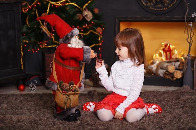 Kleines mädchen, das auf boden in schönen weihnachtsdekorationen sitzt. mädchen, das mit einem spielzeug-weihnachtsmann spielt. neujahrsvorbereitung.