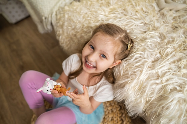 Kleines mädchen, das auf boden sitzt, der auf sofa lehnt und spaß spielt mit fingerspielzeug