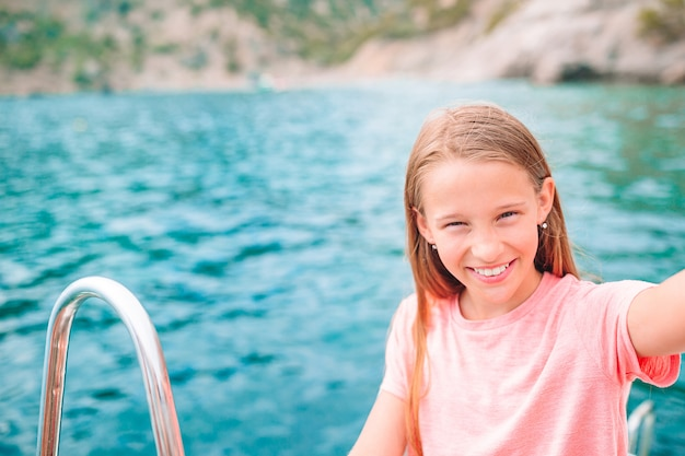 Kleines mädchen, das auf boot im klaren offenen meer segelt