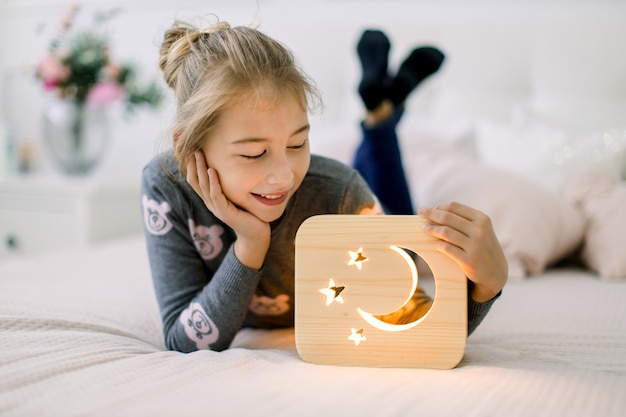 Kleines mädchen, das auf dem bett im gemütlichen hellen schlafzimmer zu hause mit stilvoller nachtlampe aus holz mit ausgeschnittenem mond- und sternenbild liegt