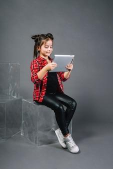 Kleines mädchen, das auf dem block betrachtet digitale tablette gegen grauen hintergrund sitzt