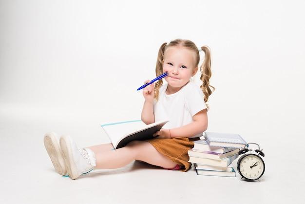 Kleines mädchen, das auf dem boden liegt und bilder in einem notizbuch isoliert zeichnet