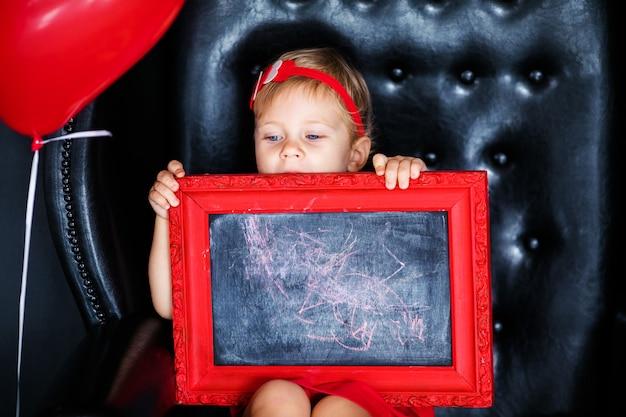 Kleines mädchen, das auf dem lehnsessel mit rotem gestaltetem bild am valentinstag sitzt
