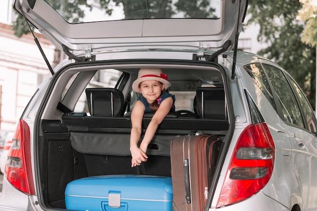 Kleines mädchen, das auf dem rücksitz eines familienautos sitzt