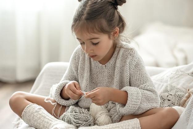 Kleines mädchen, das auf dem sofa sitzt und lernt, zu stricken, freizeitkonzept zu hause.