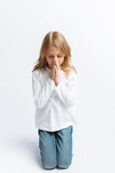 Kleines mädchen, das auf den knien zu gott betet, gemeinschaft mit gott, süß und schön