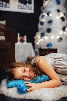 Kleines mädchen, das auf einem blauen kissen schläft. das konzept des neuen jahres und der frohen weihnachten