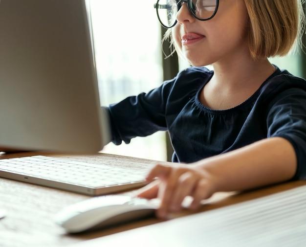 Kleines mädchen, das auf einem computer spielt