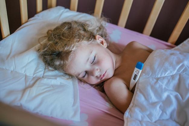 Kleines mädchen, das auf einem kissen in ihrem bett mit dem thermometer schläft