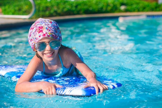 Kleines mädchen, das auf einem surfbrett im swimmingpoll schwimmt
