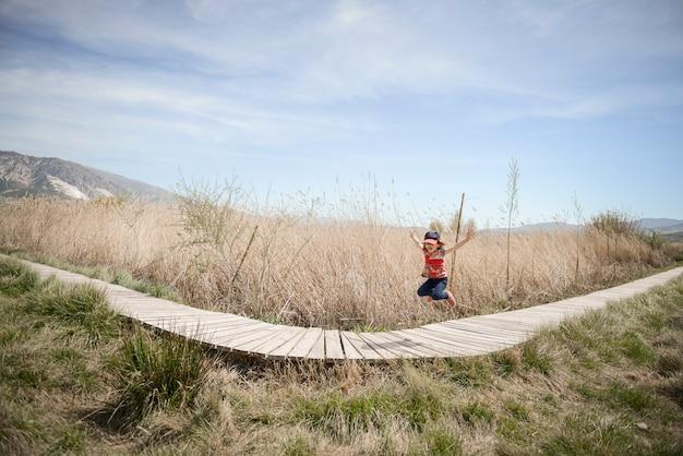 Kleines mädchen, das auf einen weg von hölzernen brettern in einem sumpfgebiet in padul, granada, andalusien, spanien geht
