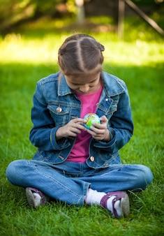 Kleines mädchen, das auf gras im park sitzt und den globus erforscht